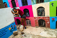 """A Mayan girl repairs parging of a niche during the bone cleansing ritual at the cemetery in Pomuch, Mexico, 27 October 2019. Every year on the Day of the Dead, people of Pomuch, a small Mayan community in the south of Mexico, visit the cemetery to take part in a pre-Hispanic tradition of cleaning of bones of their departed relatives (""""Limpia de huesos""""). People who die in Pomuch are firstly buried for three years in an above-ground tomb then the dried-up bodies are taken out, bones are separated, wrapped in a decorated cloth, put into a wooden crate, and placed on display among flowers for veneration."""