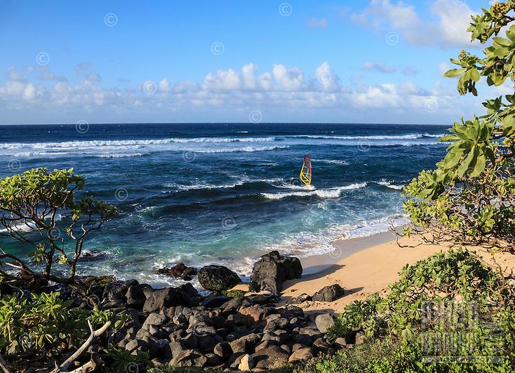 A windsurfer navigates over a reef at Ho'okipa Beach on Maui.