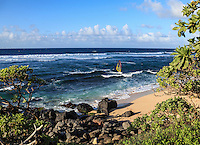 A windsurfer navigates over a reef at Ho'okipa Beach on Maui.