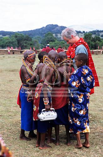 Lolgorian, Kenya. White man wearing a shukka showing something to a group of Maasai girls, one carrying a radio.