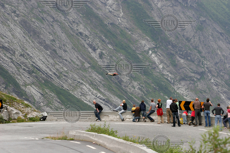 Andreas Barkhall flies past a group of tourists and BASE spotters. The mountain range of Trollstigen and Trollveggen are popular with tourist, but are also favourite destinations with BASE jumpers. Trollstigen is the name of a particularly winding mountain road popular with tourists. It has also become a popular place for BASE jumpers as the access to the mountain is fairly easy. It also one of the few places they can show off their flying skills to the public. Most other places are quite remote. Trollveggen is the only place BASE jumping is prohibited in Norway. The law is regularly ignored by jumpers who think it outdated. Norwegian BASE (Bridge, Antenna, Span, Earth - ie. parachute jumping from fixed objects) jumpers using wingsuits. First they drop vertically to gain speed, then the suits allow them fly over the sloping landscape. © Fredrik Naumann