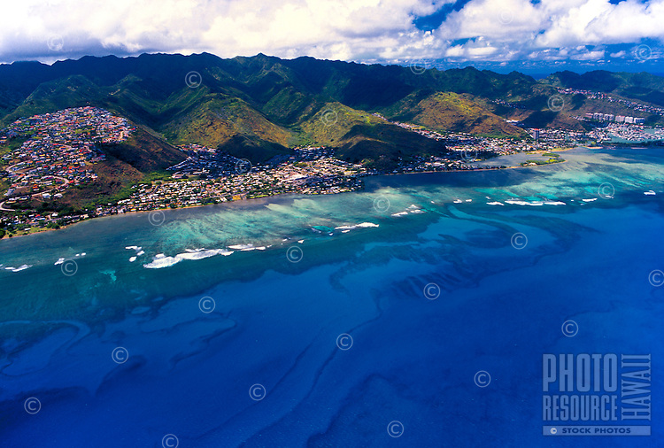 Aerial view of east Oahu with homes along the hillside mountains and wide sweeping view of the blue pacific ocean
