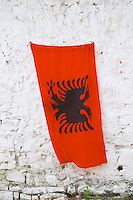 The Albanian flag, red with black double headed eagle, against a white washed stone wall. Berat upper citadel old walled city. Albania, Balkan, Europe.