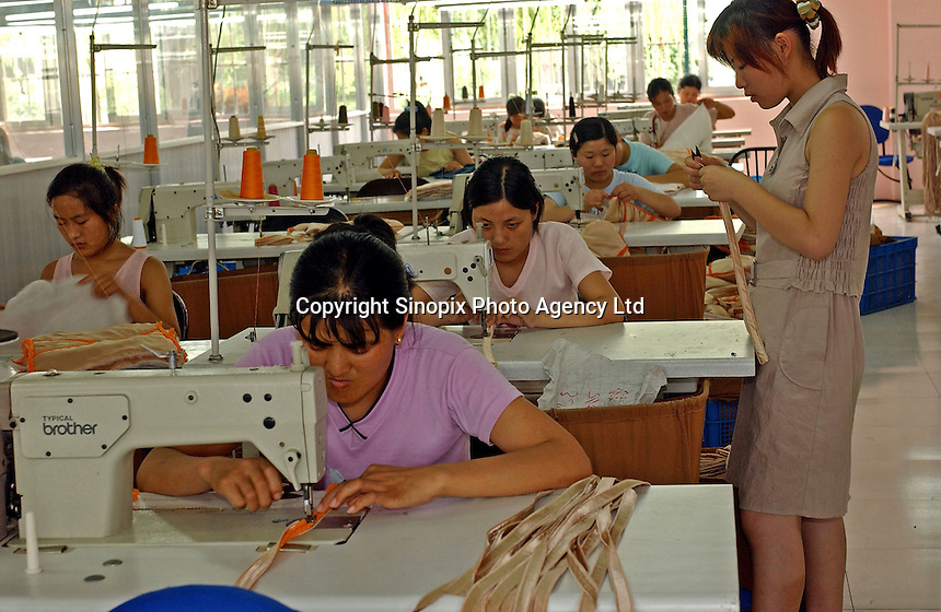 Factory workers sew bras at a French invested underwear factory on the out-skirts of Shanghai in China. Productions will be exported to England and France..29 Jun 2005