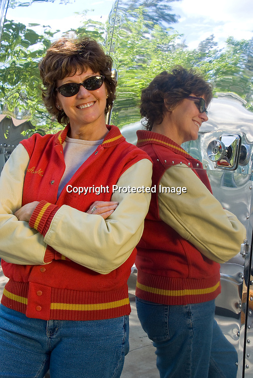 Woman leaning against a polished 1969 Airstream Caravel vintage travel trailer.