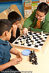 Afterschool chess program for elementary students graduates of Headstart program two boys playing one boy observing