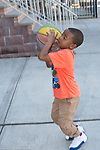 5 year old boy outside playing with basketball full length