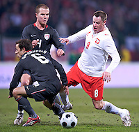 Jacek Krzynowek of Poland is defended by Michael Bradley and Steve Cherundolo of the USA. The United States defeated Poland 3-0 during an international friendly at Wisla Stadium in Krakow, Poland on March 26, 2008.