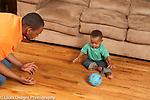Baby boy 10 months old at home playing ball game with father