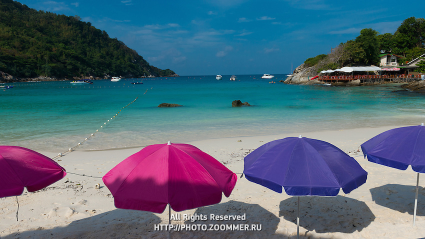 Colorful beach umbrellas on idyllic beach of Raya island, Thailand