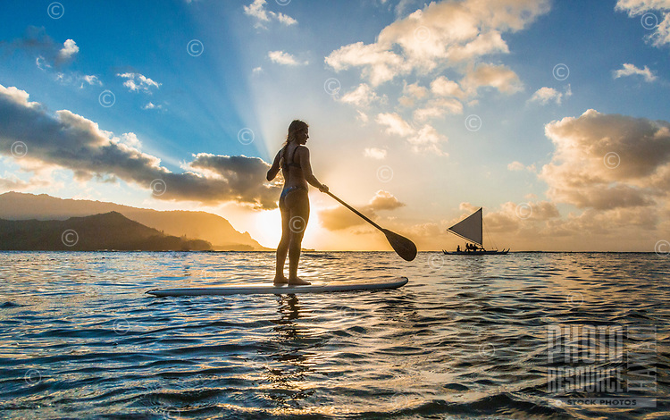 A young woman stand up paddles against the setting sun with a distant outrigger canoe passing on her right, Hanalei Bay, Kaua'i.