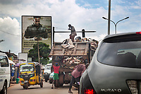"""Nigeria. Enugu State. Enugu. Town center. Traffic on the road. A garbage truck with Igbo garbage collectors loading waste on the back. A man stands on top and drinks water from a tiny plastic bag. A giant advertisement billboard for a mobile phone company. A yellow auto rickshaw used by """"Keke"""" driver for transporting people around town. The  tricycle better known in Nigeria as the Keke NAPEP is gaining the dominance on Nigerian roads sweeping every street of cities and villages. The auto rickshaw is a common form of urban transport, both as a vehicle for hire and for private use. Enugu is the capital of Enugu State, located in southeastern Nigeria. 15.07.19 © 2019 Didier Ruef"""
