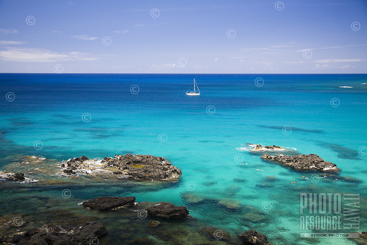 Sailboat anchored in the clear blue water of Waimea Bay on the North Shore of Oahu, with people snorkeling in the foreground