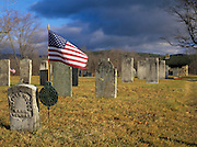 Old weathered headstones in an scenic New England graveyard with an american flag in an unknown Plymouth, New Hampshire graveyard.