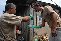 Técnicos da secretaria de saúde do estado do Pará, fazem fiscalização entrando em todas ás áreas de risco, e coletam larvas para identificação do mosquito.  o fiscal põe a bandeira amarela aviso de seu trabalho no bairro da Terra Firme ao lado do igarapé do Tucunduba, grande área de baixada onde moradores moram em favelas acima dágua. Confirmado o número de notificações em 4652 casos sendo 32 de dengue hemorrágica com 8 óbitos, diz ainda que pesquisas apontam que para cada caso notificado existem 20 sem o conhecimento da saúde pública. As principais instituições envolvidas na dateção e controle da doença  são o Instituto Evandro Chagas que faz a confirmação do diagnóstico , a secretaria do estado de saúde e o hospital Barros Barreto.<br /> Belé, Pará, Brasil.<br /> 27/04/2007<br /> Foto Paulo Santos/Interfoto
