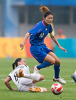 Japanese midfielder (10) Homare Sawa steps through the tackle of New Zealand captain (8) Hayley Moorwood during first round play in the 2008 Beijing Olympics at Qinhuangdao, China. .  Japan tied New Zealand, 2-2, at Qinhuangdao Stadium.