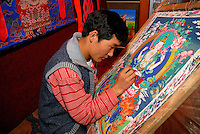 Tibetan artist painting a traditional Buddhist thangka of Chenresig, the Bodhisattva of Compassion, considered to be reincarnated in the Dalai Lama.  Different figures signify different aspects of Buddhist philosophy and are anonymously copied and re-copied.  Barkhor alley, Lhasa, Tibet.