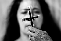 A face of a Colombian woman is seen behind the crucifix during the religious healing ceremony performed at a house church in Bogota, Colombia, 10 March 2016. Hundreds of Christian belivers, joined in nameless groups, gather every week in unmarked home churches dispersed in the city outskirts, to carry out prayers of liberation and exorcism. Community members and their religious activities are usually conducted by a charismatic pastor or preacher. Using either non-contactive methods (reading religous formulas from bible, displaying Christian symbols and icons) or rough body-pressure-points techniques and forced burping, a leading pastor commands the supposed evil spirit, which is generally believed to come from witchcraft, to depart a person's mind and body. The demon's expulsion often consists of multiple rites and may last for several months.