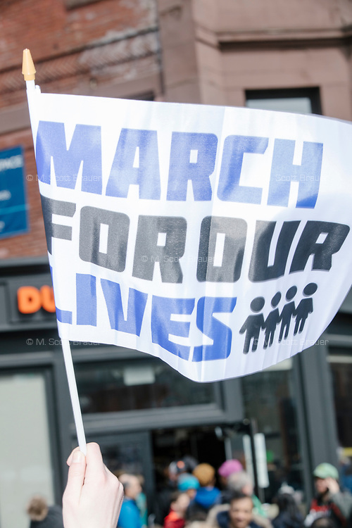 """People take part in the March For Our Lives protest, walking from Roxbury Crossing to Boston Common, in Boston, Massachusetts, USA, on Sat., March 24, 2018, in response to recent school gun violence. Here a person holds a banner reading """"March for our lives."""""""