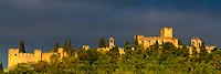 Convent of Christ (Convento de Cristo) battlements panoramic view from downtown in gold sunset light, under a beautiful stormy sky, in Tomar, Portugal