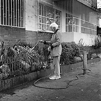 Norma uses a hosepipe to water her garden in Ora Court, Bellevue East.