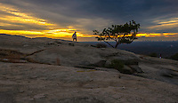Scenic landscape photograph of Stone Mountain near Atlanta Georgia. A beautiful sunset, shining golden rays to create a surreal moon like view of Stone Mountain, with the City of Atlanta in the distant horizon.