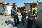 Mehmed Stefanov (left), a United Methodist local pastor, talks with a Roma family in the Maxsuda neighborhood, part of his parish in Varna, Bulgaria. Feride Ramadan Mehmed (left) and her husband Mehmed are holding their children Birdzhan, 1, and Erdzhan, 3. They are Turkish-speaking Roma, and were violently driven out of one neighborhood by racist gangs. They took refuge in a United Methodist Church for a year before finding this small house to rent.