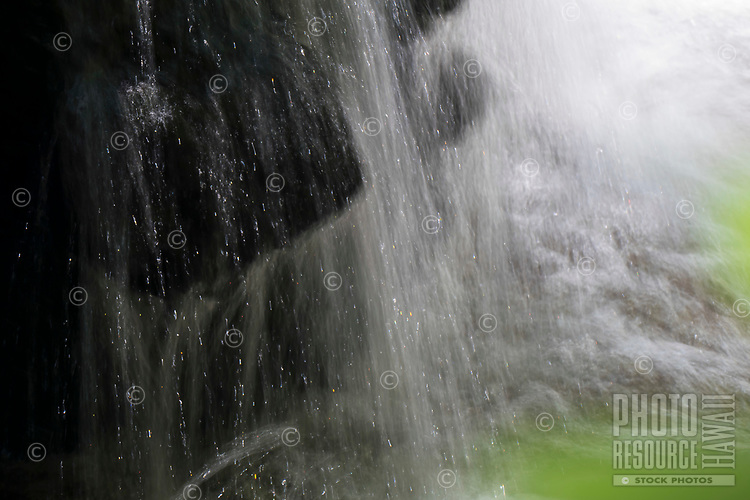 A small waterfall flows off of black rocks at Hawaii Tropical Botanical Garden in Onomea Valley in Papa'ikou near Hilo, Big Island of Hawai'i.