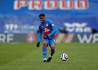 10/13th March 2021; Selhurst Park, London, England; English Premier League Football, Crystal Palace versus West Bromwich Albion; Wilfried Zaha of Crystal Palace passing the ball into midfield