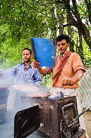 Kashmiri men grilling kabobs on small charcoal grill alongside road, Srinagar, Kashmir, India.