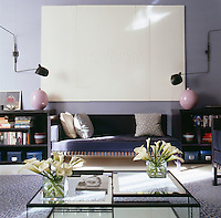 Under a large monochrome painting in the living room a banquette sofa is arranged symmetrically between matching bookcases, vases and wall lights by Serge Mouille