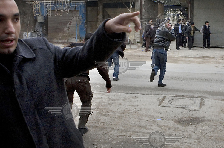 Men run across a road in the Arbin suburb of Damascus as a sniper fires down the street. The district has come under sustained attack from Government forces who have suffered many casualties themselves. Protests against the ruling Baathist regime erupted in March 2011and although they were peacefully government forces violently repressed them. In response to being commanded to shoot unarmed civilians large numbers of men deserted the army and formed the Free Syrian Army and an armed uprising began with major clashes taking place in early 2012......
