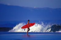 Surfer with red board about to head out to big waves on Oahu's famous north shore