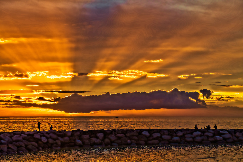 Sunrays shoot from the clouds in this sunset viewed from in front of the boat launch dock in Kihei, Maui
