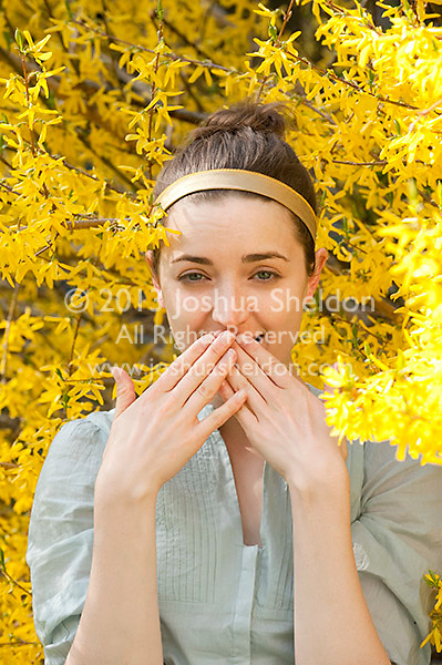 Young woman covering her mouth standing amoungst Forsythia flowers