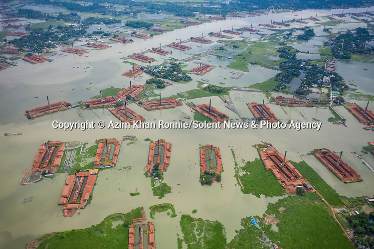 Pictured: The same brick factories post-flooding.<br /> <br /> Hundreds of brick factories appear to have nearly disappeared under water following severe flooding.  The buildings were covered with water within three days of heavy rainfall after a nearby river breached its banks.<br /> <br /> Workers were able to save thousands of bricks - but many were lost to the 20 ft deep floodwater.  Photographer Azim Khan Ronnie pictured the flooded brick factories in Zazira near his home in Dhaka, Bangladesh.<br /> <br /> Please byline: Azim Khan Ronnie/Solent News<br /> <br /> © Azim Khan Ronnie/Solent News & Photo Agency<br /> UK +44 (0) 2380 458800
