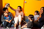 Toddler program female teacher keeping attention of children at circle time using dinosaur toy as a puppet