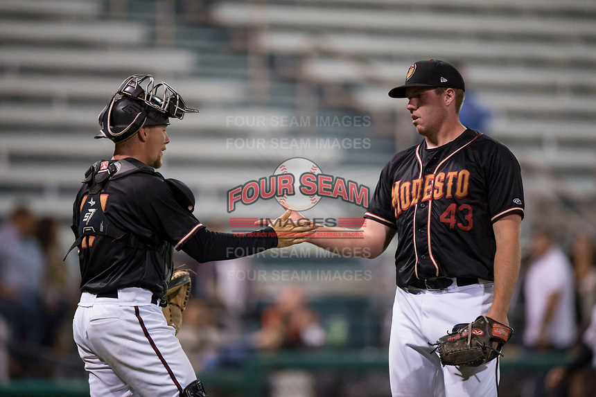 Modesto Nuts relief pitcher Seth Elledge (43) shakes hands with catcher Tyler Baker (17) after closing out a California League game against the Lake Elsinore Storm at John Thurman Field on May 11, 2018 in Modesto, California. Modesto defeated Lake Elsinore 3-1. (Zachary Lucy/Four Seam Images)