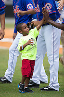 A young fan high fives Kingsport Mets players after throwing out the ceremonial first pitch prior to the game against the Greeneville Astros at Hunter Wright Stadium on July 7, 2015 in Kingsport, Tennessee.  The Mets defeated the Astros 6-4. (Brian Westerholt/Four Seam Images)