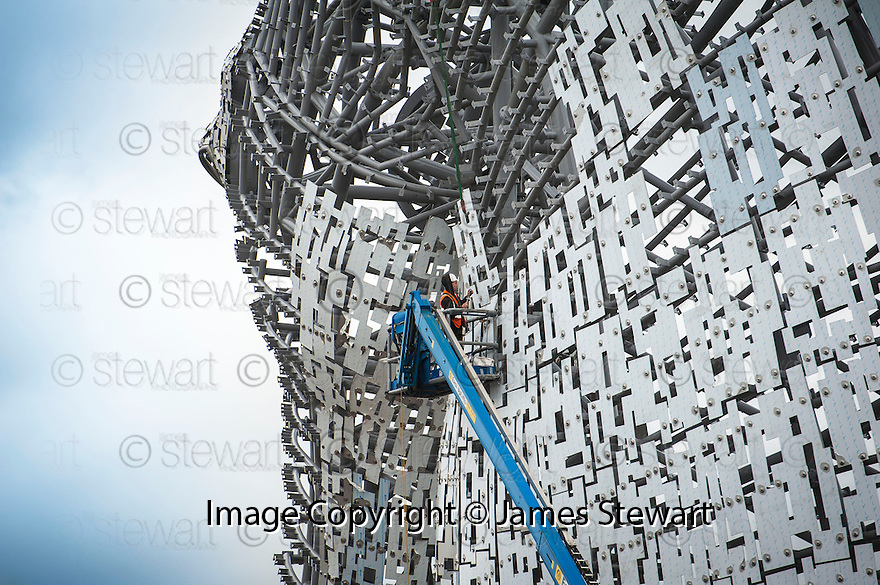 A construction worker puts on the outer skin.