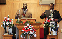 Assistant to the paster Yves Ruterera, left, smiles alongside pastor Peter Chege, right, as they say a prayer during Sunday service at The Africa Lighthouse Baptist Temple near Stony Point in Albemarle County, VA. The small 10 family congregation is made up of African refugees and immigrants who's service is spoken in Swahili and translated into English. They've just signed a rent-own lease for a small church after meeting for three years at a local school. Photo/The Daily Progress/Andrew Shurtleff