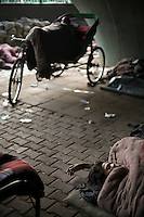 People sleep on the ground and in rickshaws beneath a bridge near the banks of the Yamuna River.