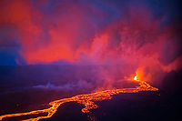 lava originating from Kilauea Volcano, erupts in a fountain from fissure 8 in Leilani Estates, near Pahoa, at dusk, and flows as an incandescent lava river through lower Puna into Kapoho, Puna, Big Island, Hawaii, USA