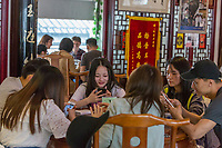 Suzhou, Jiangsu, China.  Young Chinese Adults Checking their Cell Phones in the Tong De Xin Noodle Restaurant.