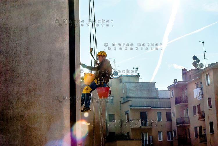 Milano, periferia nord, ristrutturazione della facciata di un palazzo. Muratore lavora sospeso da una fune --- Milan, north periphery, renovation of a building's facade. Worker suspended from a rope
