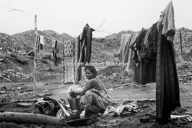 A lady washes cloth at Bokapahari in Jharia, Bokapahari is getting destroyed by mine fire. Jharkhand, India