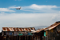 An airplane flies over the shacks of the slum of Cité Soleil, Port-au-Prince, Haiti, 11 July 2008. Cité Soleil is considered one of the worst slums in the Americas, most of its 300.000 residents live in extreme poverty. Children and single mothers predominate in the population. Social and living conditions in the slum are a human tragedy. There is no running water, no sewers and no electricity. Public services virtually do not exist – there are no stores, no hospitals or schools, no urban infrastructure. In spite of this fact, a rent must be payed even in all shacks made from rusty metal sheets. Infectious diseases are widely spread as garbage disposal does not exist in Cité Soleil. Violence is common, armed gangs operate throughout the slum.