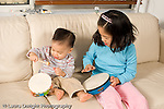 16 month old toddler boy with sister age 8 playing musical instrument hitting tambourine with a drum stick as sister hits another tambourine with her hand vertical
