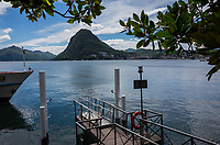 Switzerland. Canton Ticino. Lugano. Tourist boat's landing stage. View on Lake Lugano and the Monte San Salvatore. Lake Lugano (Italian: Lago di Lugano or Ceresio) is a glacial lake. The Monte San Salvatore (912 m) is a mountain in the Lepontine Alps above Lake Lugano and the city of Lugano. 28.04.2019 © 2019 Didier Ruef