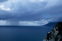Rainy storm clouds hover over the sea on the Amalfi Coast, Italy.